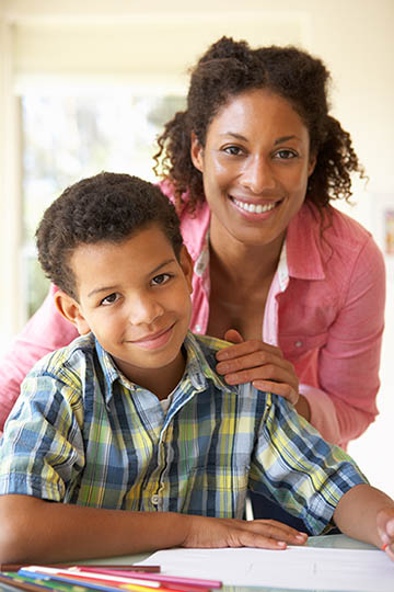 Mother Helping Son With Homework At Home