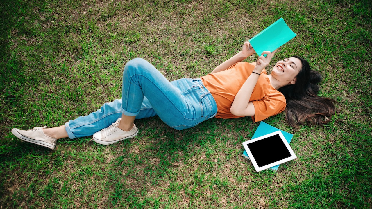 Student in a park studying with notebook and tablet