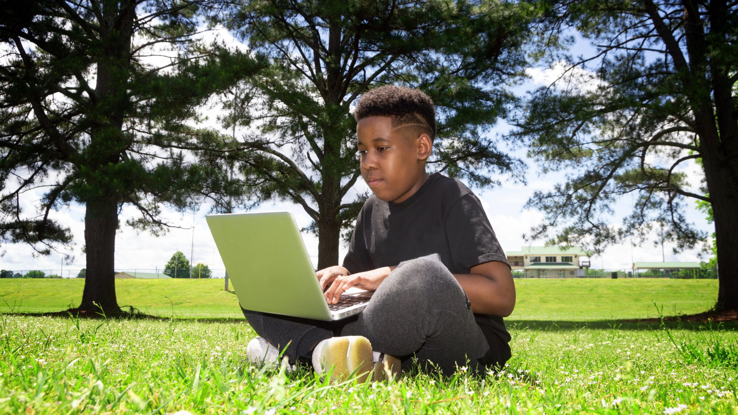 Student sitting in a grassy park doing online summer school with a laptop.