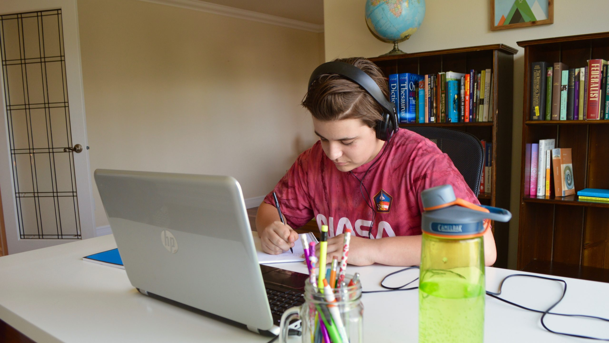 ALVS student learning at home with laptop, school supplies, books on a shelf and a globe.